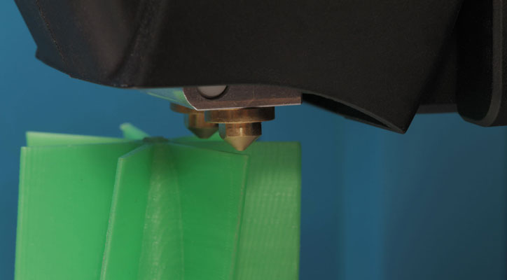 Closeup of the printer head and 3D printed Lego-like construction blocks